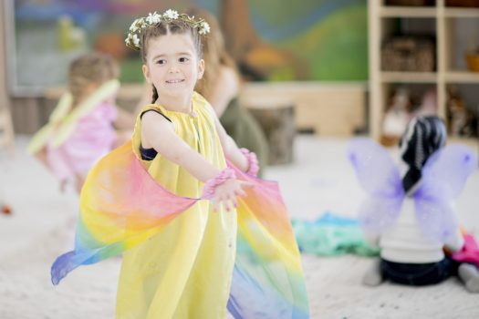Elementary school girl dances in class, wearing flowers in her hair and a long flowing dress