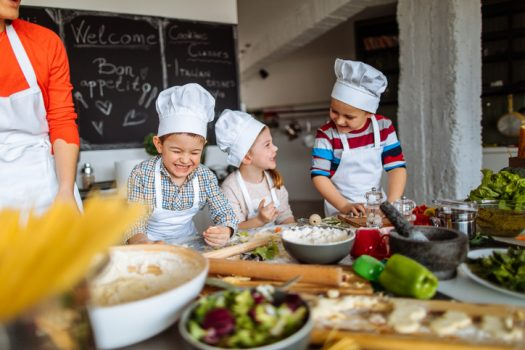 Children learning to cook with a chef.