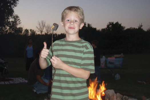 Child at camp holding burnt marshmallow.